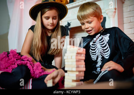 Handsome little boy and his pretty elder sister wearing Halloween costumes sitting on floor of living room and playing - Stock Photo