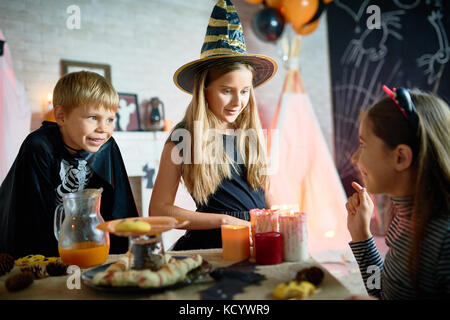 Profile view of pretty girl telling scary story to her little friends while celebrating Halloween at home, table - Stock Photo
