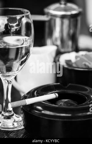 Black and White Monochrome Images of a Glass of White Wine With an Ashtray and Cigarette on a Table In a Cafe or - Stock Photo