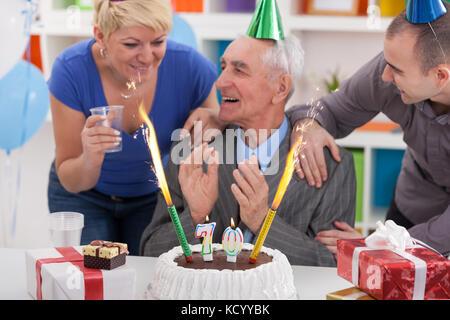 Senior man celebrating birthday with his family - Stock Photo