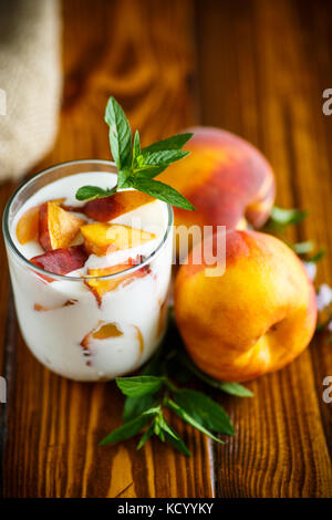 Sweet home-made yogurt with pieces of peach - Stock Photo