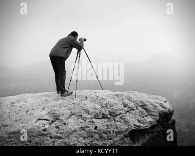 Wildlife photographer on mountain summit works. Man like to travel and photography, taking pictures of moments during - Stock Photo