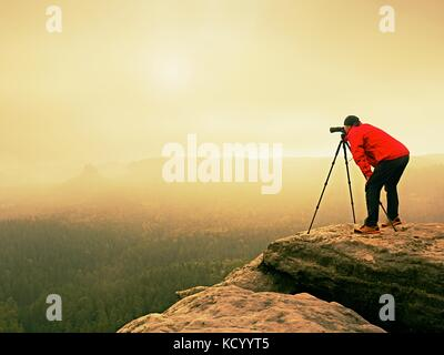 Professional photographer work on mountain peak. Nature photographer takes photos with mirror camera on rock above - Stock Photo