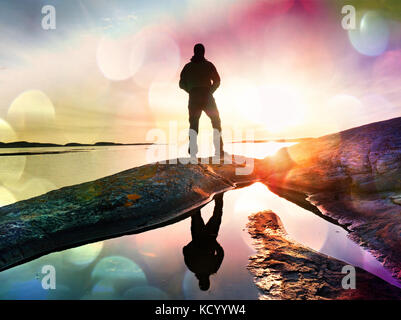 Lens defect.  Tall backpacker watch clear sunny spring daybreak over sea. Hiker with backpack stand on rocky shore - Stock Photo