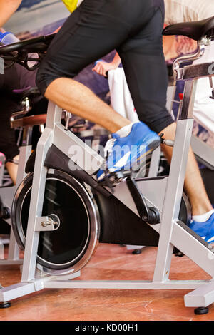 man in gym doing exercising on bike - Stock Photo