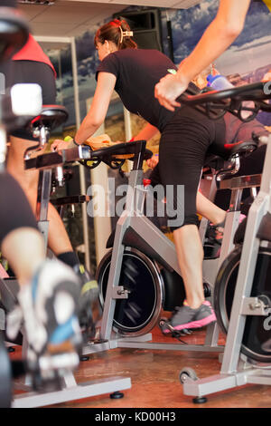Group of people spinning in the gym, exercising their legs doing cardio training - Stock Photo