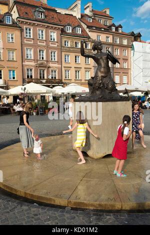 Children playing around the Mermaid Statue in the Old Town Square of Rynek Starego Miasta, Warsaw, Poland, - Stock Photo