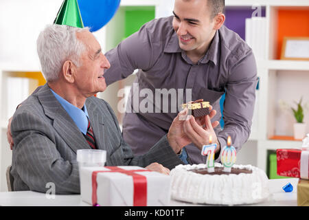 Smiling senior man receiving gift for birthday at home - Stock Photo
