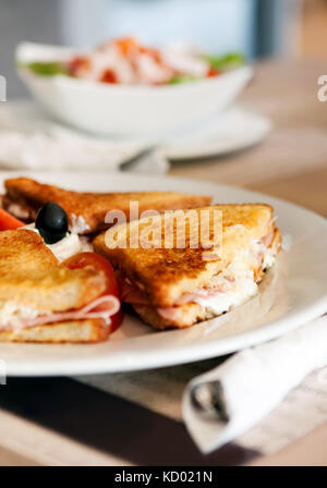 A plate with a delicious prosciutto panini with tomato, mozzarella cheese, olive and mayonnaise, served with a side - Stock Photo