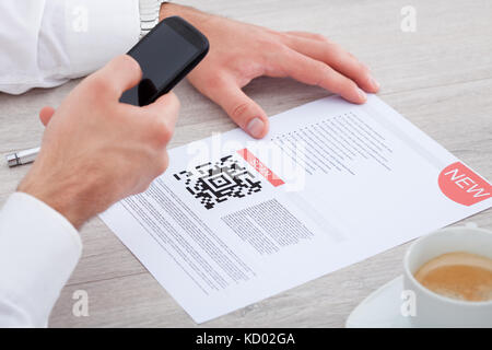 Close-up Of Hand Holding Mobile Scanning Bar Code - Stock Photo