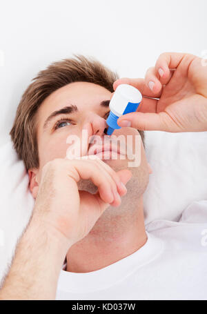 Close-up Of Young Man Using Nasal Spray - Stock Photo