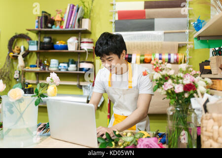 Happy asian male florist using laptop at counter in flower shop - Stock Photo