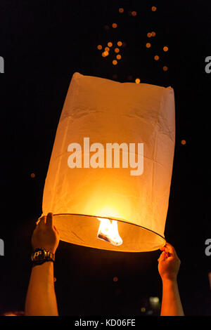 Thai people release Khom Loi, the sky lanterns during Yi Peng or Loi Krathong festival in Chiang Mai, Thailand. - Stock Photo