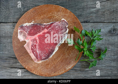 Raw dry aged t-bone steak from beef with parsley on rustic wood - Stock Photo