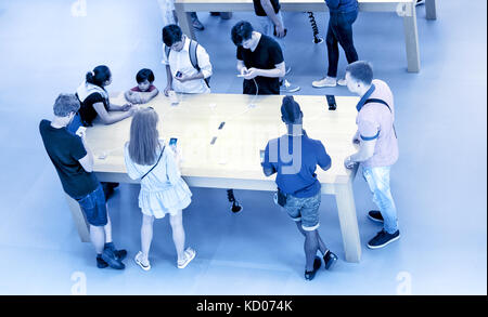 People are trying out devices put on display in an Apple store. - Stock Photo