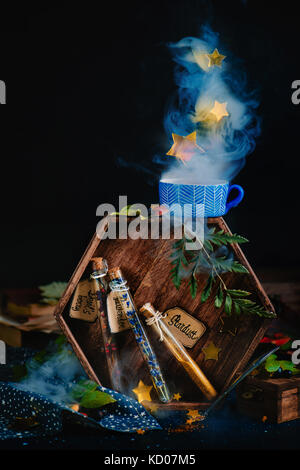 Test tubes with potion ingredients, lavender, berries, and stardust. Magical still life with staming cup of herbal - Stock Photo