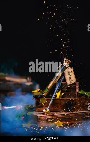 Stardust test tube with wooden boxes in a magical still life with golden glitter and stars. Wizard TABLE concept - Stock Photo