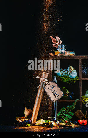 Mystic still life with a test tube of stardust and wooden case with magical items and potion ingredients. Wizard or witch table with pixie dust. Fairy tale concept with dark background and copy space.