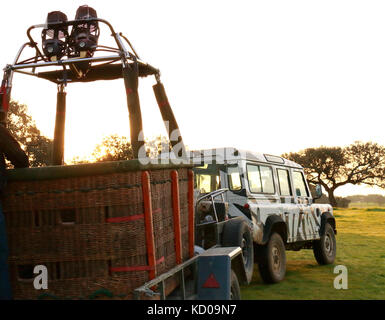 Basket of a hot-air balloon with burners above, towed by an off-road vehicle - Stock Photo