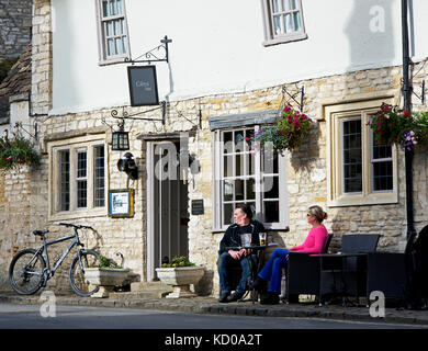 Couple sitting outside the Castle Inn, Castle Combe, Wiltshire, England UK - Stock Photo