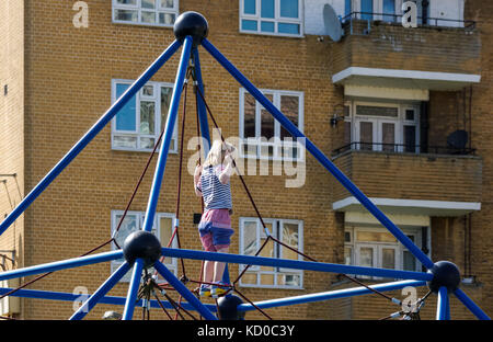Young girl playing on playground at council estate in Stoke Newington, London, England United Kingdom UK - Stock Photo