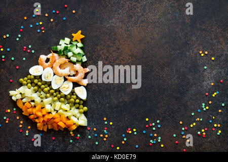 Christmas tree from a salad olivier on a brown rusty stone or metal background. Top view with a copy. - Stock Photo