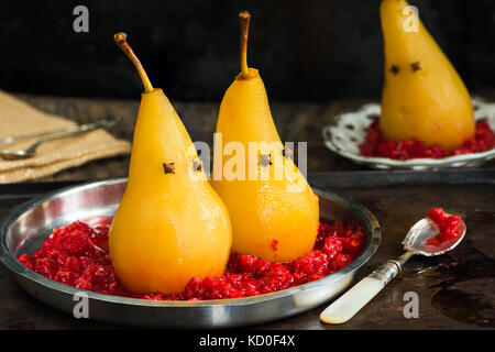 Pears poached in sweet syrup on crushed raspberries, presented as ghosts. Halloween food idea. - Stock Photo