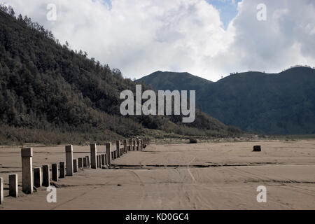 Grey poles sticking out of the volcanic brown sand landscape at the foot of the active Volcano mount Bromo at the - Stock Photo