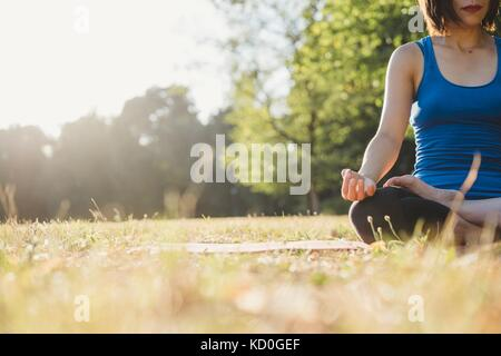 Mature woman in park, sitting in yoga position, low angle view - Stock Photo