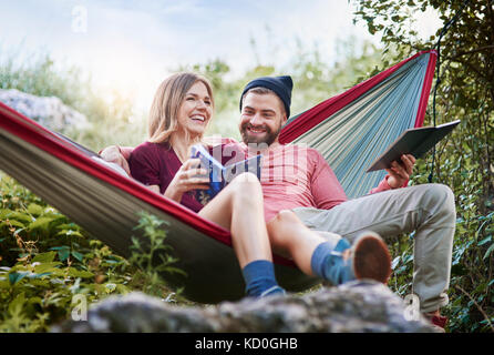 Couple relaxing in hammock, smiling, Krakow, Malopolskie, Poland, Europe - Stock Photo