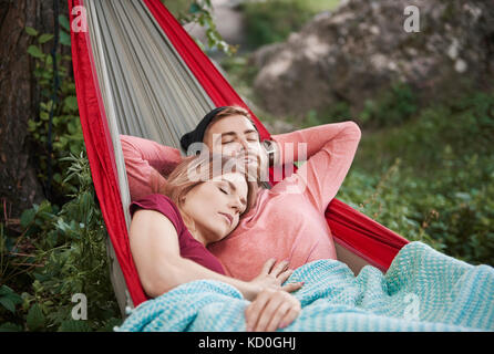 Couple relaxing in hammock, eyes closed sleeping, Krakow, Malopolskie, Poland, Europe - Stock Photo