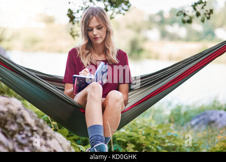 Woman sitting in hammock writing in notebook, Krakow, Malopolskie, Poland, Europe - Stock Photo