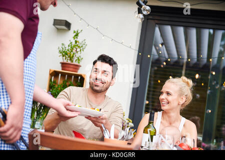 Man handing plate to couple with baby daughter at family lunch on patio - Stock Photo