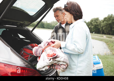 Mature couple removing camping equipment from car boot - Stock Photo