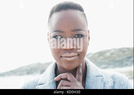 Portrait of young woman in coastal setting, finger under chin - Stock Photo