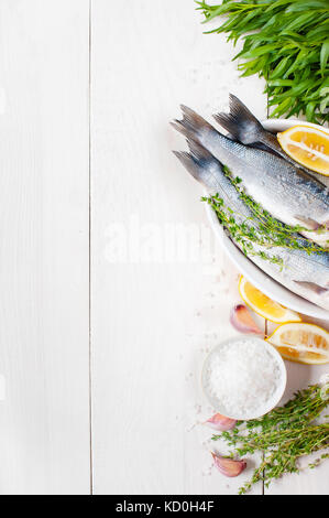 White wooden background with fresh raw fish and ingredients - Stock Photo
