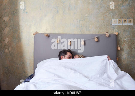 Couple in bed, under the covers, kissing - Stock Photo