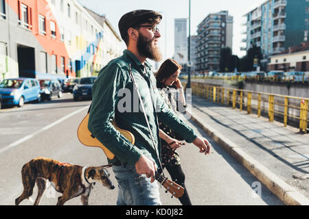 Cool couple walking dog by city canal - Stock Photo