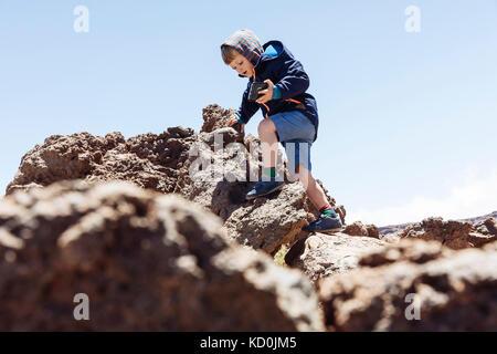Boy clambering up rocks at Mount Teide, Tenerife, Canary Islands - Stock Photo