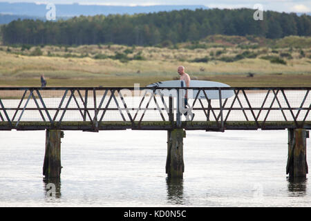Surf boader walking across iron bridge at the popular surfing beach of Lossiemouth in Scotland during pleasant warm - Stock Photo