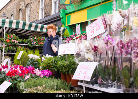 Young man selling flowers and plants in an outdoor stall in the famous Columbia Road Flower Market, near Hackney - Stock Photo
