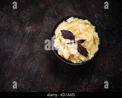 Mashed potatoes in dark bowl with fresh red basil on black concrete background. Top view or flat lay. Copy space. - Stock Photo