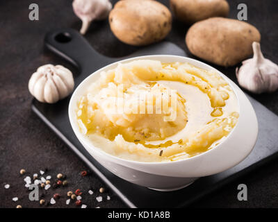 Mashed potatoes with spices and olive oil in white bowl on black cutting board over dark concrete background - Stock Photo