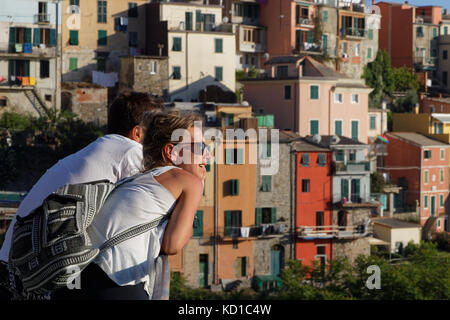CORNIGLIA, Italy, June 3, 2017 : A young couple admires a romantic view of the Cinque Terre National Park on the - Stock Photo
