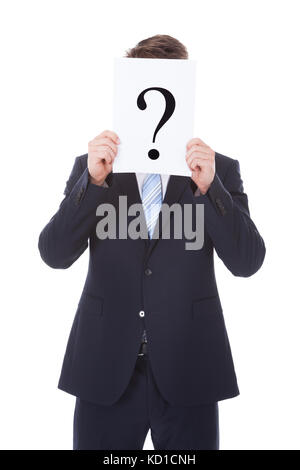 Portrait Of Businessman Holding Question Mark Sign In Front Of Face - Stock Photo