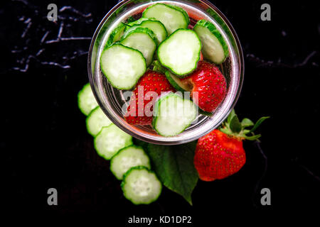 Cucumber and strawberry detox water in glass on black background. Diet. Top view - Stock Photo