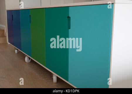 Movable kitchen island on wheels, painted in ombre colours - Stock Photo