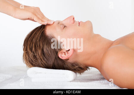 Portrait Of A Young Man Getting Head Massage In Spa - Stock Photo