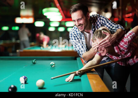 Young couple playing together pool in bar - Stock Photo