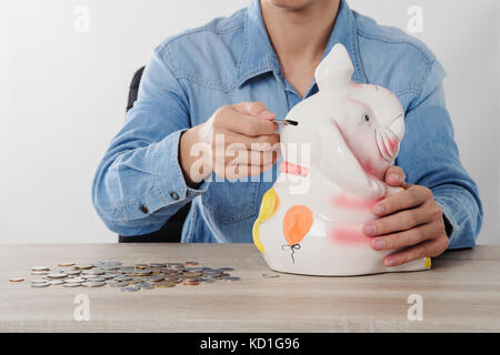 Hand putting money coins in to Elephant Bank money saving finance concept - Stock Photo